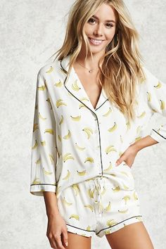 A PJ set featuring an allover banana print on a woven shirt, contrast piping, a notched collar, button front closures, and 3/4 length sleeves, as well as a pair of matching woven shorts with contrast piping, and a drawstring elasticized waist.