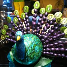 Watermelon peacock food sculpture with grapes and kiwi fruit. Head is carved from a big potato.