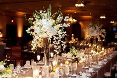 tall centerpieces...i like how the small white flowers spill over
