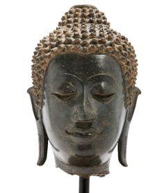 Siam, deuxième style de Sukhothai à Chieng Mai, XIVe-XVe siècle Tête du Bouddha en bronze de belle patine verte, les cheveux coiffés en boucles serrées surmontée de l'ushnisha, les oreilles aux longs lobes.   (Manque la flamme).   H. 17 cm  Certificat de J.-C. Moreau-Gobard du 12/07/2001