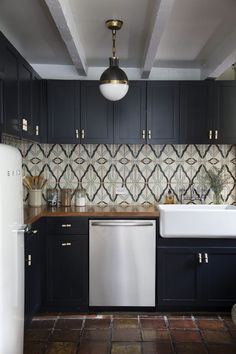 Two types of terra-cotta tiles give the kitchen in this New York apartment personality: Traditional clay-like slabs lend European charm, while patterned tiles add interest behind the sink.