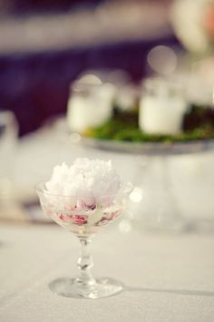Gorgeous single bloom centerpieces - like the look of the cake stand with grass and candles in the background too!