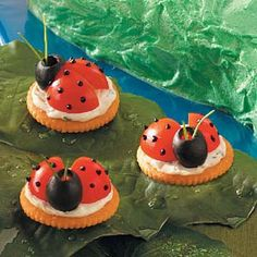 Cherry tomato quarters form the wings of these ladybugs.  A ripe olive is the head. They are perched on a cracker spread with a seasoned cream cheese mixture.