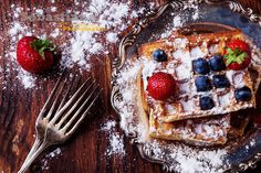 Belgian Waffles - Home made Belgian waffles served on vintage metal plate with berries (strawberry and blueberry) and sugar powder