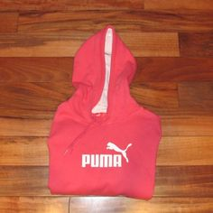 Puma signature hoodie Size medium. Muted red/pink color. White logo on chest with single, thin white line on underside of sleeves that runs down the sides. Small, white Puma logo on the upper, right side of the back and tiny silver PUMA button on back of bottom, left corner. Front pocket drawstring hood. 80% cotton and 40% polyester. Length from shoulder to bottom measures 22 inches. Arm length from shoulder to sleeve measures 23.5 inches. Width from armpit to armpit measures 18.5 inches…