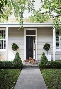 A neutral palette was adopted for the entryway and exterior of this traditional Victorian home with white trims helping to make the black front door pop.