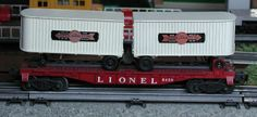Lionel postwar # 6430 flatcar with two white Cooper-Jarrett trailers.