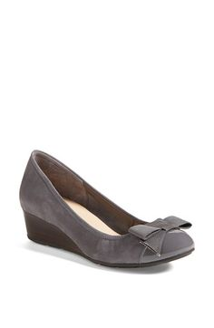 Cole Haan 'Air Tali' Wedge Pump  A grosgrain bow and a patent-glossed cap toe bring ladylike sophistication to a stylish pump that features an elastic-perfected fit. The modest wedge heel provides demure lift, and is deceptively comfortable thanks to a cushioned sole enhanced with Nike Air® technology. Founded in Chicago, Illinois in 1928, Cole Haan is known for producing stylish, classic shoes with an emphasis on comfort.