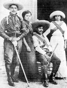Soldiers and soldaderas pose for a photo. Given his trim uniform and sword, the man on the left is probably an officer. The women wear their rebozos crossed to resemble the cartridge belts of the men. This was the badge of soldaderas. The appearance of these women indicates they were probably middle-class revolutionaries. Often such women were educated and were motivated by ideology as much or more than a simple desire to accompany their men.