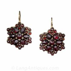 Bohemian Garnet Earrings, Whether perceived as snowflakes or six-pointed stars, these delightful Bohemian garnet earrings will glisten day and night. Gilt metal with 14K ear wires, 11/16 inch.
