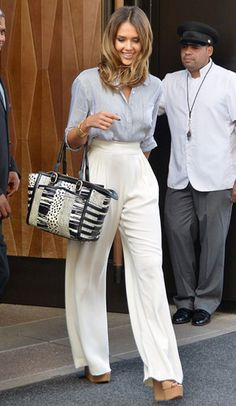 Jessica Alba wearing wide leg pants and a delicate blouse