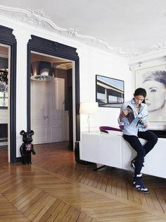 idee deco mur, décoration murale salon, grand portrait photo d'un visage de femme en noir et blanc, parquet classique de vieux appartement de Paris, portes larges aux bords accentués de peinture noire, ours en porcelaine noir entre les deux portes, plafond blanc riche en frises arabesques et feuilles