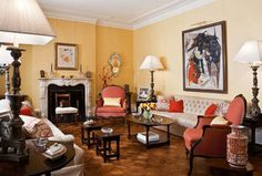 Decorating with Yellow, Old-World Burnished Yellow Walls ~ An old-world design is articulated in the living room against a backdrop of warm yellow-gold walls. The traditional color is appropriate for showcasing a collection of 19th-century art.  Traditional Home Magazine, Interior design: Marcy Masterson