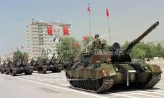 A Turkish tank unit, passes by during Victory Day celebrations in Ankara on Saturday, Aug. 30, 1997. A portrait of modern Turkey's founder Mustafa Kemal Ataturk is seen in the background. (AP Photo/Burhan Ozbilici)
