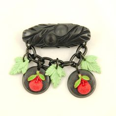 Retro Cherries Fakelite Brooch:This is a beautiful retro reproduction bakelite-inspired novelty brooch by Charcoal Designs. The hand cast resin brooch features carved cherries medallions and green leaves hung from a black enameled chain that is attached to a black carved style bar. The back has a silver metal locking clasp and the brooch measures approximately 2.5 inches by 2.25 inches. Made in the... $26.00