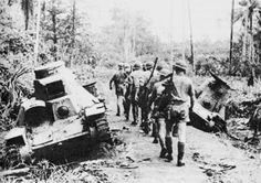 Australian Riflemen Passing Abandoned Japanese Tanks The photo was taken at Milne Bay New Guinea September 1942 on the track to Rabi. The patrol is from the 61st Battalion of the 7th Australian Infantry Brigade