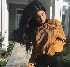Interesting look: The 18-year-old Keeping Up With The Kardashian's star was sporting a ribbed and ripped thick cropped sweater as she raised her arm in the air to expose her abs and a hint of bra