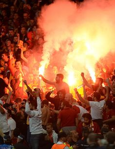 Galatasaray fans jump up and down as they set off flairs in the stands at the Emirates Sta...