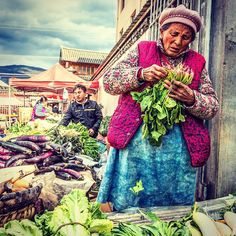 At the weekly market in Shaxi (沙溪 Yunnan province China. Every Friday farmers come from their nearby villages to Shaxi to sell their produce. This woman is of the Bai (白 minority ethnic group as evidenced by her signature blue apron.