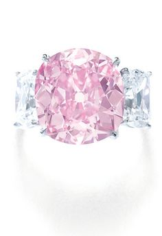 The Historic Pink'  Magnificent fancy vivid pink diamond ring Set with a cushion brilliant-cut fancy vivid pink diamond weighing 8.72 carats, between cushion brilliant-cut diamonds weighing 1.09 and 1.12 carats, size 52.