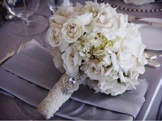 The bridal bouquet will be a clutch bouquet of white hydrangeas, white garden roses, white dendrobium orchids, white dahlias, and white ostrich feathers wrapped in ivory ribbon all the way to the ends of the stems with jeweled brooch accent.