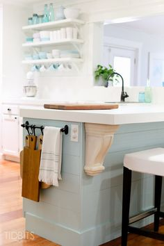 Cottage Fresh Kitchen, by TIDBITS With touches of wood tones, splashes of blue Planked island painted BM Soft Chinchilla, subtle gray/ blue. Chunky corbels from Home Depot painted with white wash pickling stain. Pine shelves with IKEA brackets painted white on one side, rustic reclaimed shelves on other, farmhouse IKEA sink, IKEA lighting hack, IKEA barstools, white square tile from lowes, cupboards and drawer fronts professionally sprayed, DIY on cabinet boxes painted