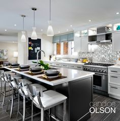 A large island offers ample counter seating.  Unobtrusive yet conveniently located on the back side of the island you'll find the dishwasher and microwave drawer. #candiceolson