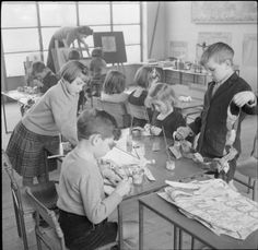 English children making Christmas chains from scraps of old paper & painted newspapers. (1944)
