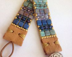 Beautiful Teals, Greens, Blues, Sage, Turquoise Gold Sundance Style, Southwestern Style Hand Loomed Beaded Bracelet. Use Zoom Under Photos To See Detail. Faceted Glass Czech Beads, Seed Beads, Leather End Tabs, Bronze Tree Of Life Button. Quality Made. Very Durable. Measures 7 1/2 Inches In Length. Width- 7/8 Inches. Will Fit Wrist Size Up To 6 1/2 Inches This Is Not Adjustable. Ready For Gift Giving Shipped In A Very Cute Bracelet Gift Box. Ships Priority One Mail Listing Green Z