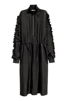 Атласное платье с оборками: Прямое атласное платье из смесового хлопка. На платье рельефный воротник стойка и молния сверху. Длинные рукава с двойными оборками, а также рельефной трикотажной резинкой. Кулиска на талии и боковые карманы. Без подкладки.