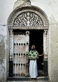 Veiled woman in front of a door in Stone Town, Zanzibar, Tanzania by Eric Lafforgue