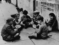 Homeless children play a card game on a Paris sidewalk during World War II.