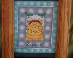 A cartoon gray kitty wearing a smart and stylish Santa hat. A red Christmas boarder is at the top and bottom. The fuzzy part of the hat is covering one eye - to much eggnog perhaps?  Stitched on 14 count white aida cloth and framed in a white wood look 3 1/2 X 5 table top frame.