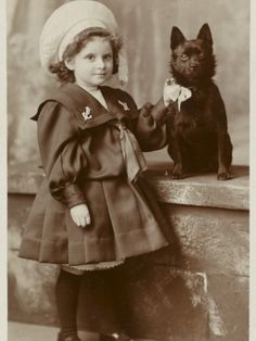 A Small Girl in a Sailor Suit Poses with Her Schipperke  Kinda wanna fame this in a nauticle frame for my interior