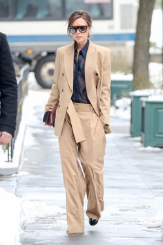 Victoria Beckham con traje masculino 'oversize' nude con camisa semitransparente azul