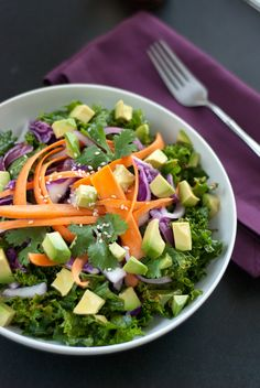 raw salad made with kale, avocado, carrots, and sesame seeds