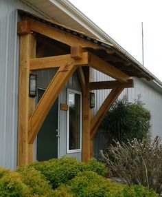 This timber frame porch and awning are located at our Homestead Timber Frames office and shop in Crossville, TN. Come by and see authentic, hand crafted timber framing in action! -- Homestead Timber Frames Timber Frame Porch - Timber Frame Awning - Heavy Timbered Porch - Homestead Timber Frames - Crossville Tennessee