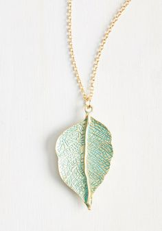 Traveling can be stressful, but this golden necklace eliminates the need to pack any other accessories - one less thing to worry about! Supported by a long cable chain and brushed with turquoise paint, the veiny leaf pendant of this timeless decoration symbolizes a spirit as carefree as the wind.