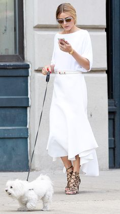 Olivia Palermo hit the streets of New York City with her dog Mr. Butler wearing a white boatneck top tucked into a decoratively seamed skirt topped off with a matching belt. She accessorized her look with translucent Westward Leaning sunglasses, an intricate pair of Aquazzura lace-up heels, gold timepiece, and her sparkling engagement ring.