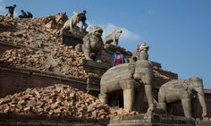 Nepalese visitors walk on ruins near the Nyatapola temple in Bhaktapur. The temple itself survived