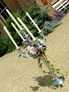 Vintage candelabra with pink roses, lisianthus and ivy trails.