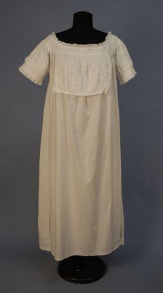 Ca.1860 cotton chemise with over-corset flap trimmed with puffings, tucks, whitework embroidery at CF, and drawn work on ruffles. Whitaker Auctions.