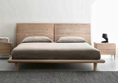 A gorgeous modern bed characterized by a wooden headboard divided into two elements with gradually growing thickness. Front feet can be chosen between wooden or metal type.