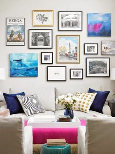 Black and white and colour photographs and canvases over a neutral sofa in this gallery wall with pops of pink, green and blue.