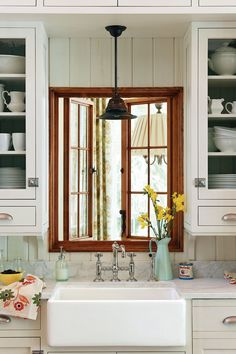 """Just above this kitchen's apron-front sink, a dark-stained window stands out in a warm hue. Thinned paint coats walls, ceilings, and cabinetry to create the patina of weathered wood. See more of this New Old House Love it? Get it!Sink: 30"""" Single Bowl Farmer Sink by Barclay (barclayproducts.com)"""