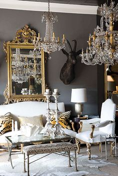 These rich dark walls complement the opulent multitude of chandeliers and extravagantly detailed gold mirror, making the room feel cozy, intimate and luxuriously grand, all at the same time. Inspired!