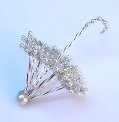 Vánoční deštníček stříbrný otevřený 2 Deštníček je vytvořen ze stříbrných tyčinek, bílých perliček a stříbrného rokailu.Délka i s rukojetí 7 cm. Deštníček je vyroben podle starého vzoru.