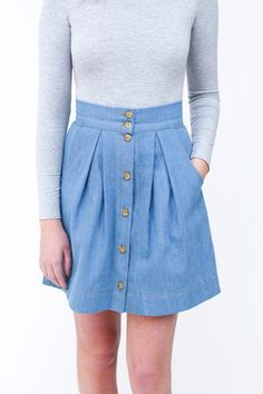Button front pleated skirt with pockets. Pattern sits on the natural waist and features button front placket, wide waistband, large scoop pockets and pleating i