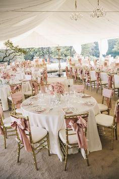 Pink and white wedding reception under a tent with hanging lamps decor | Una recepción en blanco y rosa con una carpa de tela y lámparas de araña colgantes.