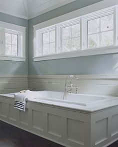 his built-in tub is flanked on all sides by high windows that provide privacy while allowing sunlight to filter into the room. The paneled tub adds texture and class to the bathroom. The silver faucet in the center enhances the graceful atmosphere. Pairing the white tub with the baby blue painted walls creates a quiet elegance in the room.